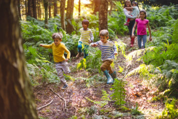 Group of children at summer camp running through a woodland area with their guide/teacher walking behind them.