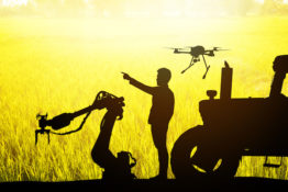 Smart farm agriculture precision technology concept. Silhouette of farmer , automation robot arm machine , uav drone , tractor truck and rice field background. Flare light effect.